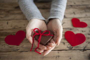 Women have a chocolate with a red ribbon