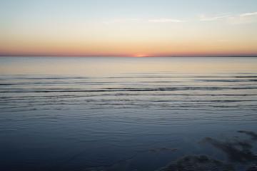sunset above sea shot from beach