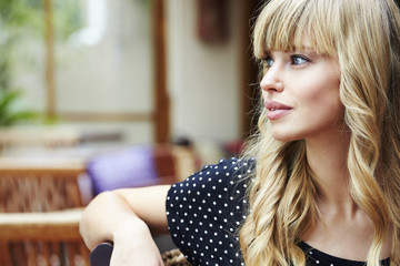 Wall Mural - Blond young woman in cafe, looking away