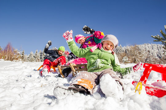 Happy children sledding at winter time. Group of children together.