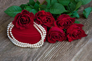 Red  gift box and necklace  on  wooden background.  Valentine's day, wedding or birthday  concept