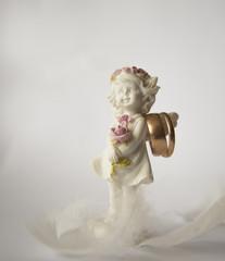 Little angel girl holding wedding gold rings on white background