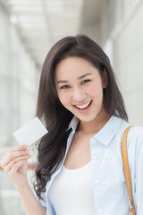 Asian woman holding a card in her hand