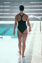 Swimmer walking by the swimming pool