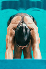 Female backstroke swimmer starting race, holding onto swimming start block