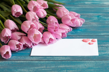 bouquet of pink tulips lie on texture painted in blue color table, next to a white envelope and three pink handmade sugar hearts