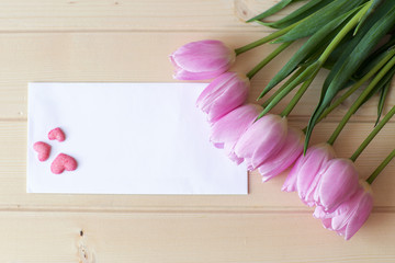 bouquet of pink tulips lie on natural wooden texture table, next to a white envelope and and three pink handmade sugar hearts