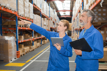 Man and woman in warehouse, pointing to shelf