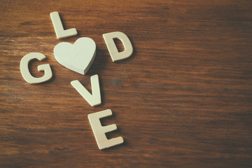 selective focus photo of The words love is god made with block wooden letters on wooden background. religion concept
