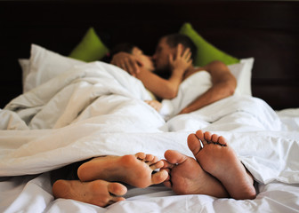 Lovely couple kissing in bed, focus on feet