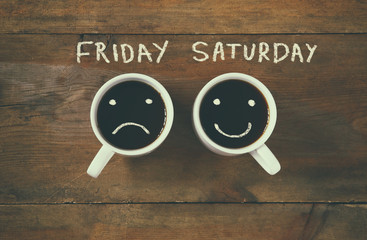 "coffee cup with sad and happy faces next to ""friday saturday"" phrase background. vintage filtered. happy weekend concept"