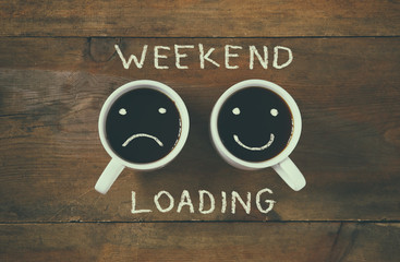 """coffee cup with sad and happy faces next to """"weekend loading"""" phrase background. vintage filtered. happy weekend concept"""