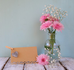 fresh white and pink flowers, heart next to vintage empty card over wooden table