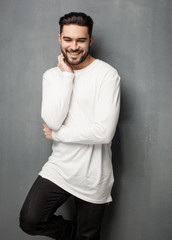 sexy fashion man model in white sweater, jeans and boots smiling