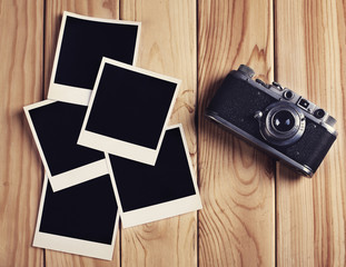 Vintage film camera and two blank photo frames on wooden table.