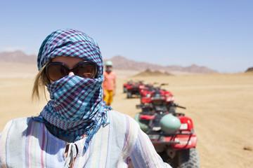 Девушка/женщина в арафатке/бедуинском платке и солнечных очках в пустыне, на заднем плане - квадроциклы