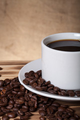 Coffee beans and coffee in white cup on wooden table opposite a