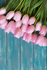 bouquet of pink tulips lie on texture painted in blue color table