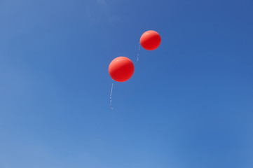 Two red balloons flying in a bright blue sky