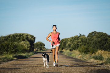 Sporty woman and dog running together on country road on summer sunset. Cheerful female athlete training and exercising outdoor with her pet.