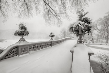 Black & White view of the Bow Bridge in Central Park covered in snow during the blizzard of January 2016. Freezing winter in Manhattan, New York City