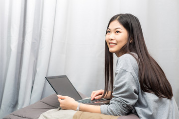 Portrait of attractive asian young lady sitting on bed uing lapt