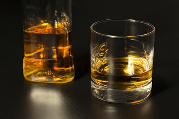 a glass of whiskey and bottle on dark table