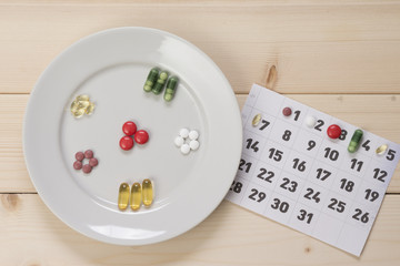 Plate with pills and a calendar