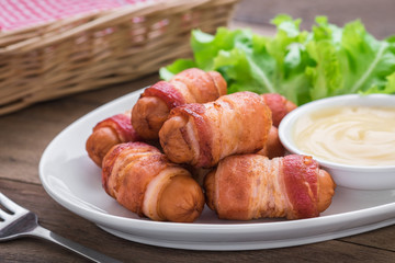 Sausages wrapped with bacon and dipping sauce