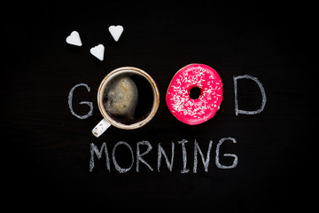 Donut, cup of coffee and heart shaped sugar cubes. Good morning greeting written on black chalk board. Table top view. Breakfast food concept. Valentines day