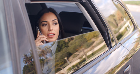 Beautiful young business woman in conversation on phone while sitting in rear seat of limousine looking out from window