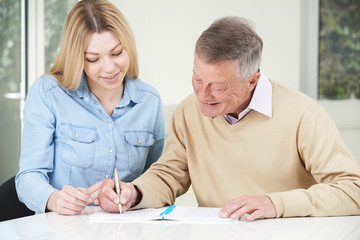 Senior Man Playing Completing Sudoku Number Puzzle With Teenage