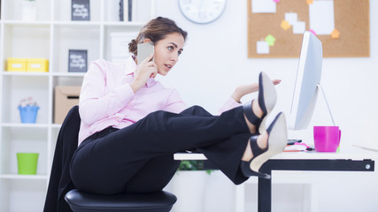 Brunette businesswoman with legs on the desk phoning in office,small depth of field