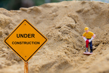 small figure of a man digging land with Under Construction message,land digger.