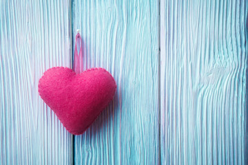 Fabric heart over blue wooden background