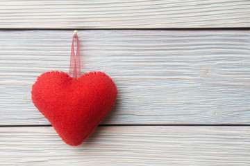 Fabric red heart over rustic wooden background