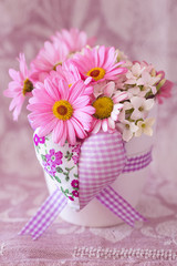Beautiful daisy flowers in a vase decorated with a heart on a beautiful tablecloth.