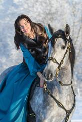 Fototapete - Woman in a blue dress riding on a grey stallion