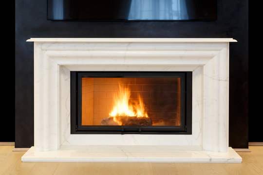 white, marble fireplace and burning fire.