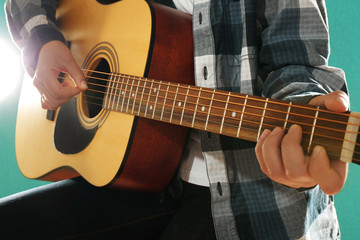 Musician plays guitar on blue background, close up