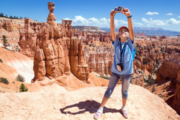 Girl photographs on the camera mountain landscape. Bryce Canyon