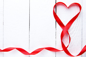 Heart shape red ribbon on white table.