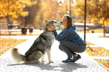 Happy young woman walking with her dog in park