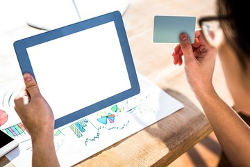 Rear view of hipster businessman using tablet and credit card