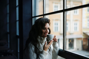 Close up portrait of young beautiful happy woman drinking coffee and looking through the window. Model wearing classic stylish knitted  winter clothes.