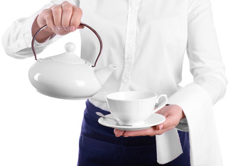 Waiter pouring tea into cup on white background