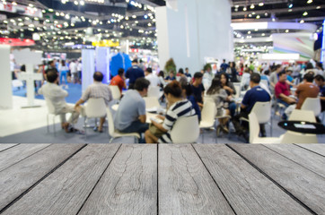 white wood table with blurred event background