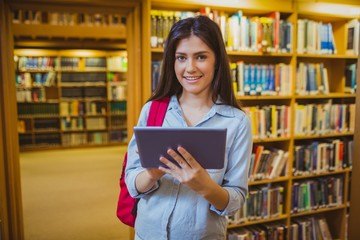 Brunette student using her tablet next to bookshelves