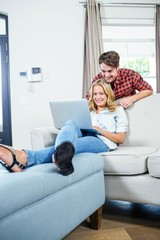 Couple using laptop on the couch