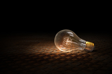 Light bulb on brick surface